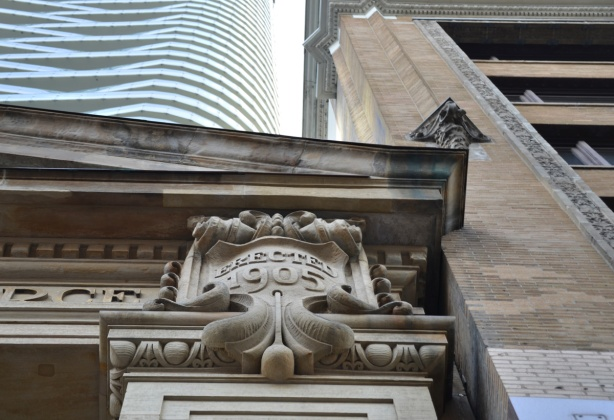 looking up at relief sculpture and column on an old building that says erected 1905, a new condo tower is behind it