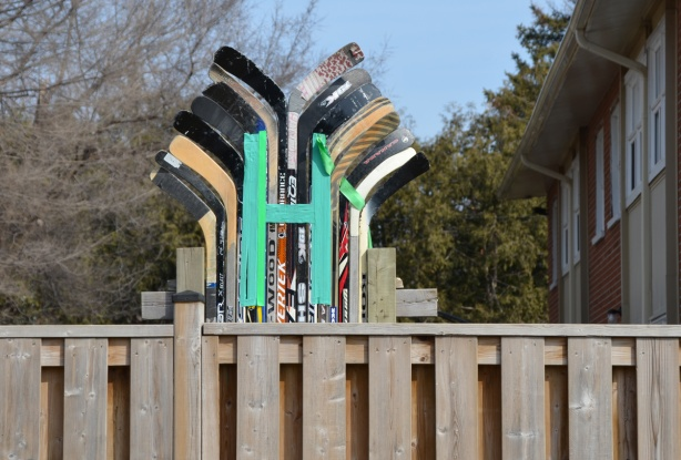 a teal coloured, large H in front of an arrangement of hockey sticks, artwork on the top of a wood fence