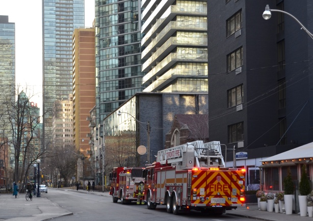 two fire trucks parked on a street of high rise and midsized apartment buildings
