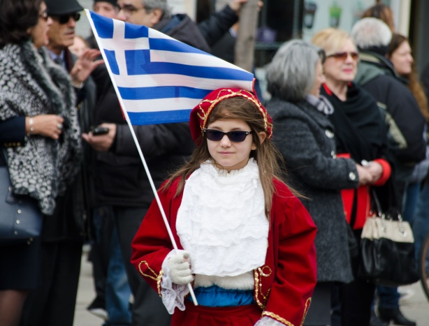 a girl in red jacket and cap, dark sunglasses, and holding a Greek flag, walks in a parade, with people on the sidewalk watching in the background.