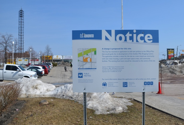 blue and white toronto development notice sign on a section of grass by a parking lot, stores in the distance