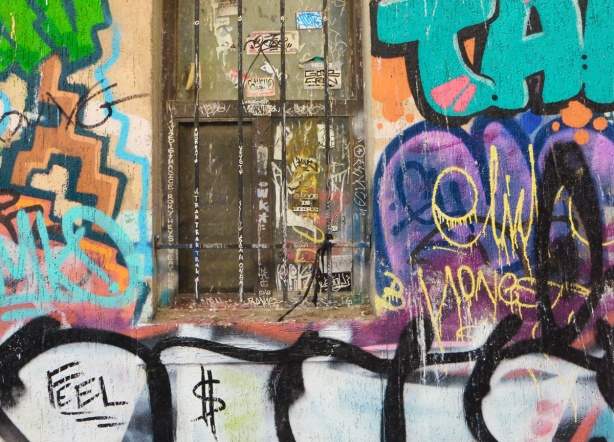 an old window with stickers on it and rusted bars in front of it, graffiti all around it