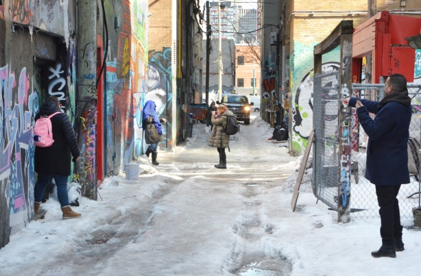 people taking pictures in graffiti alley