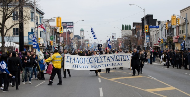 a police man in yellow jacket directs a group of marchers in the Greek Independence Day parade on the Danforth. The group is walking with a large banner with words written in Greek