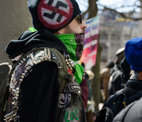 a man wears a green and brown bandana over the bottom part of his face and a black hat with an anti-nazi symbol on it.