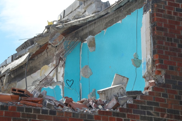 a small black heart drawn on the blue walls of building now being demolished