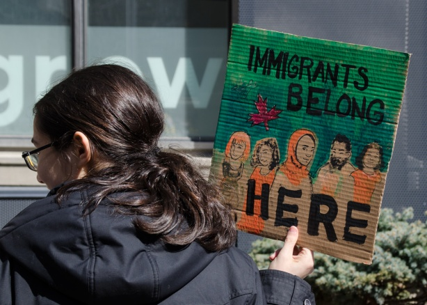 a woman holds a small painted sign that says immigrants belong here