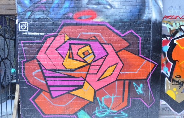 a large stylized rose in a mural in a lane