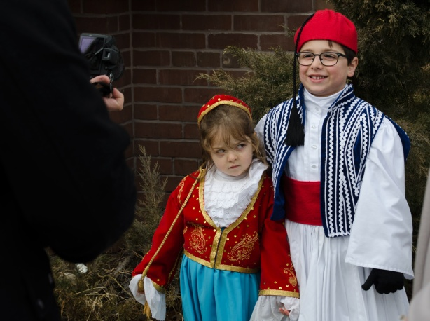 two kids in traditional Greek costume pose for a picture. The young girl is not amused.