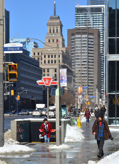 looking at the northeast corner of King Street and University Ave., entrance to St. Andrew subway station, a man is coming up the stairs and out of the station, Canada Life building and other tall buildings in the background