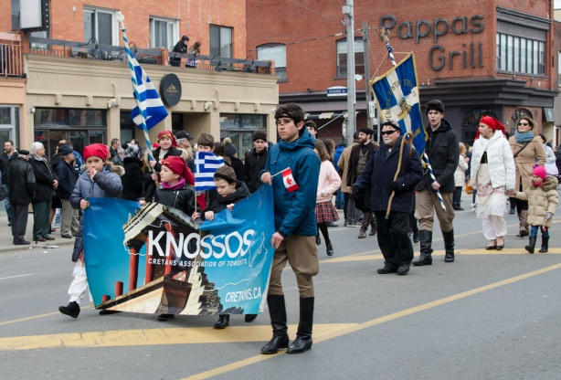 in a parade, people (mostly young boys) carrying a banner for the Knossos society (of Crete), along the Danforth, Greek flags, other people watching