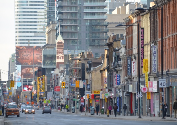 looking south on Yonge street on a sunny morning, sun is shining on the St. Charles tavern clock tower, tall buildings behind it