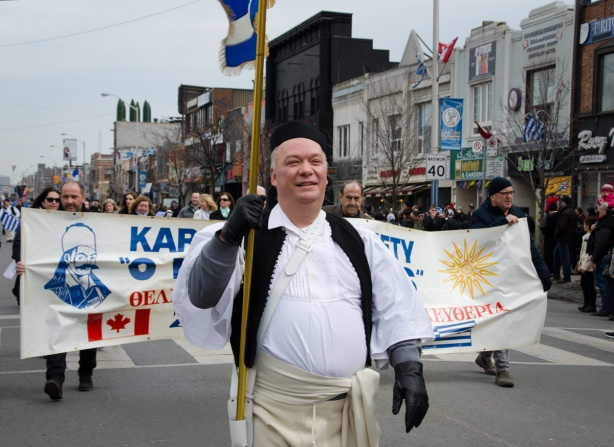 a man in traditional Greek clothing carries a flag in a parade, he is in front of a group carrying a banner