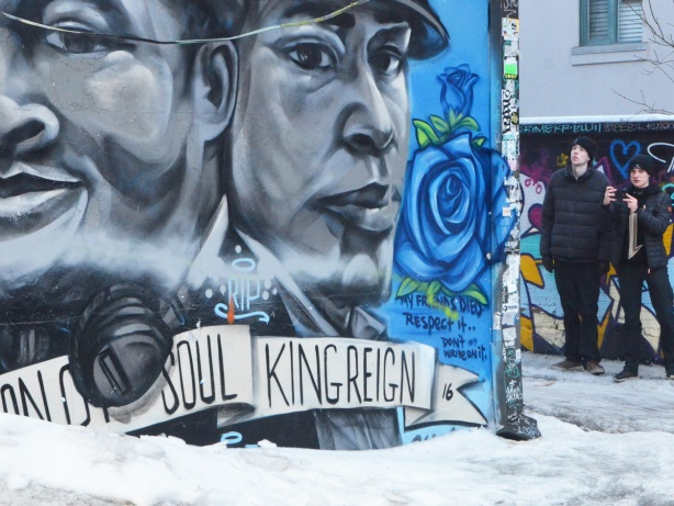 2 young men looking at street art in a lane, a large mural with two black and white mens faces in the foreground