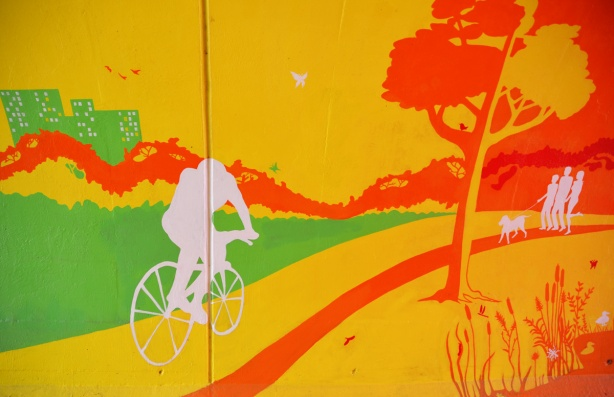 scenes from the mural painted inside the rainbow arch bridge - a cyclist on a bike rides along a yellow and orange path past yellow and orange trees