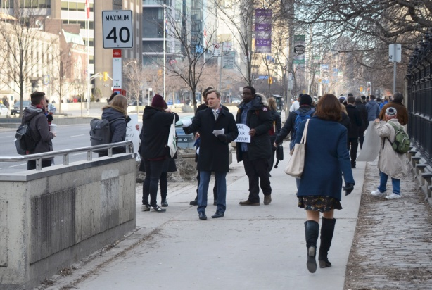people handing out leaflets and brochures at Osgoode station, on the sidewalk outside the station exit. University Ave