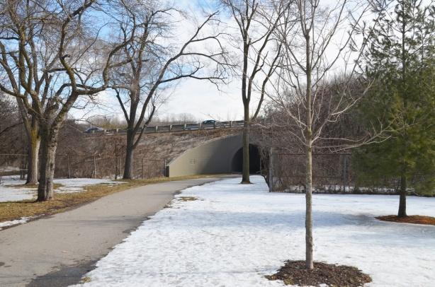 park in winter with a path that leads to a bridge under a road