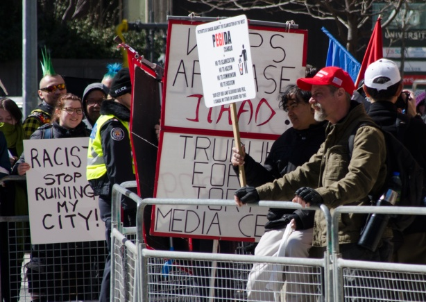 a man in a red MAGA baseball cap stands on one side of a metal barricade