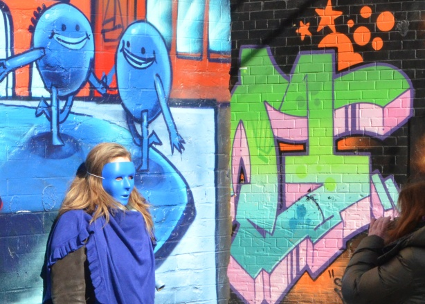 a young woman in a blue mask poses in front of an Uber5000 mural