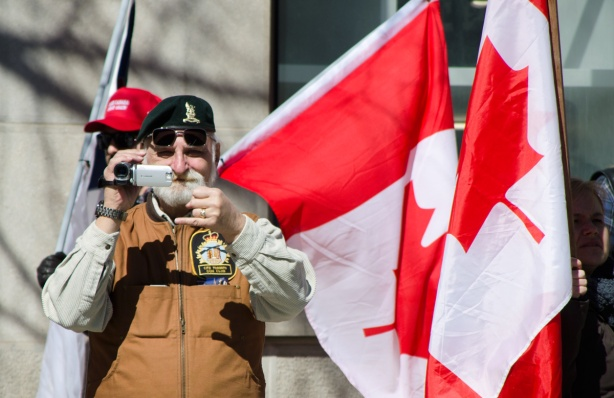 man filming crowd at a protest, two Canadian flags beside him