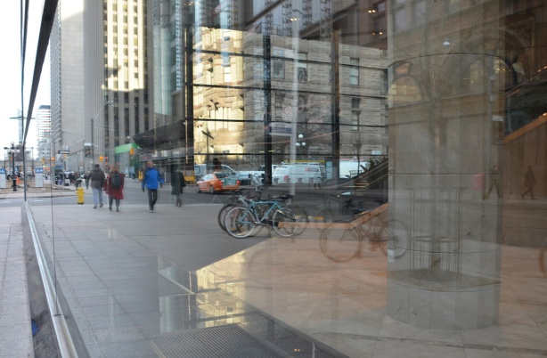 reflections in the large window of a building, people, bikes, and old city hall