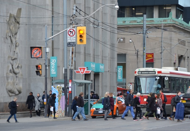 people crossing the street in front of a streetcar that is waiting for a red light. At thewest side of intersection of Queen and University