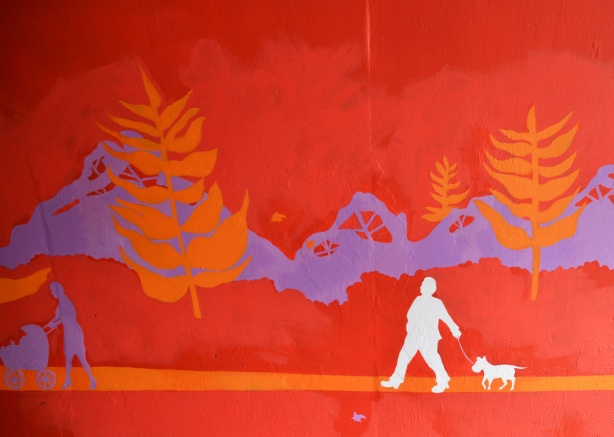 scenes from the mural painted inside the rainbow arch bridge - on red background, with orange and purple trees, a man walks his dog and a woman pushes a stroller