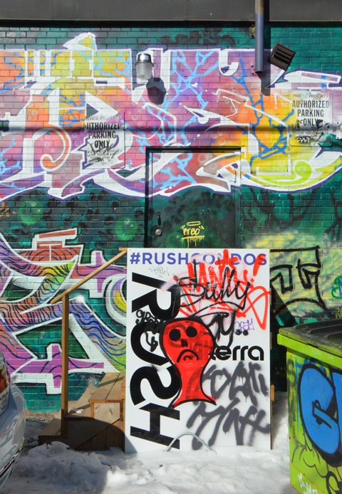 a sign advertising new Rush condos has been defaced, it is against a wall with street art and graffiti on it