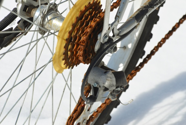 close up of rusty bicycle gears and chain, bike is parked in the snow