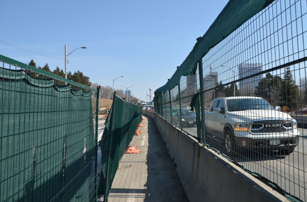green netting and fencing on both sides of a narrow sidewalk running between construction and traffic.
