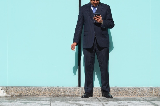 a man in a suit and tie is standing outside, his back to a bright turquoise wall, he is looking at his phone and has a cigarette in the other hand, shadows,