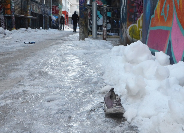 a lone beige running shoe on the ground beside a pile of snow in Graffiti alley