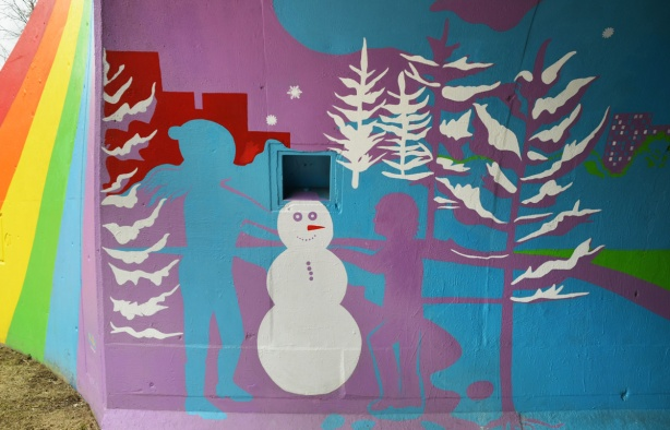 scenes from the mural painted inside the rainbow arch bridge - blue and purple children build a white snowman with white trees in the background