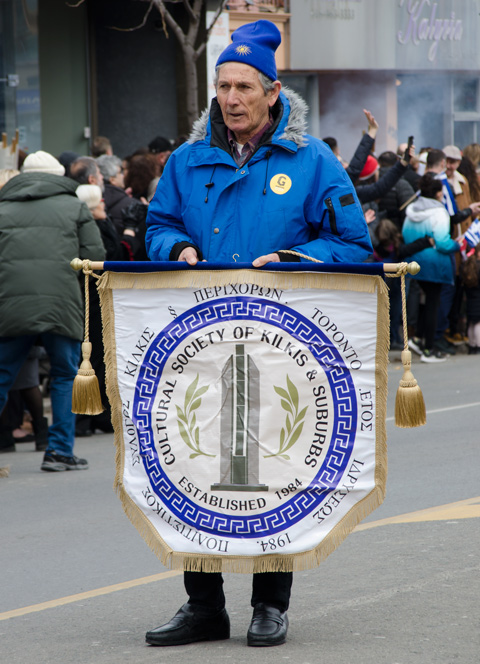 a man in a blue parka carries a banner in a parade, a small flag-like banner for the Cultural Society of Kilkis