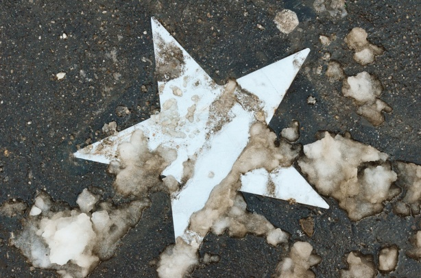 a white star on the dark sidewalk, with dirty slush on top of it in blotches