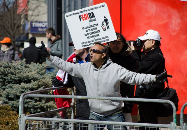 a brown skinned man in a grey sweatchirt mocks the crowd at a protest rally