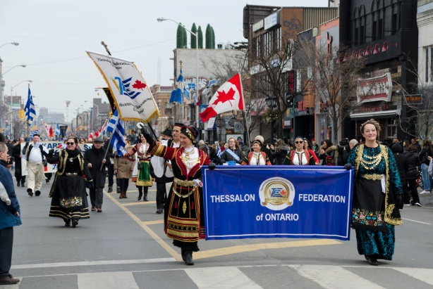 women in traditional Greek costume carry a banner of the Thessalon Federation of Ontario, a blue banner, in a parade, while others walk behind the banner