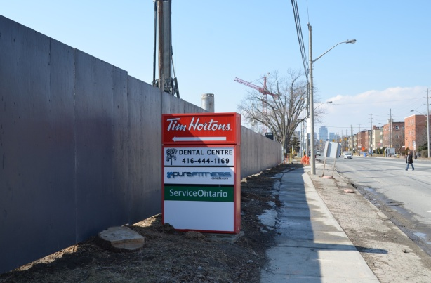 red and white tim hortons sign with an arrow pointing left at a long grey fence around a construction site, sidewalk, street, and low rise buildings on the right, Eglinton Ave