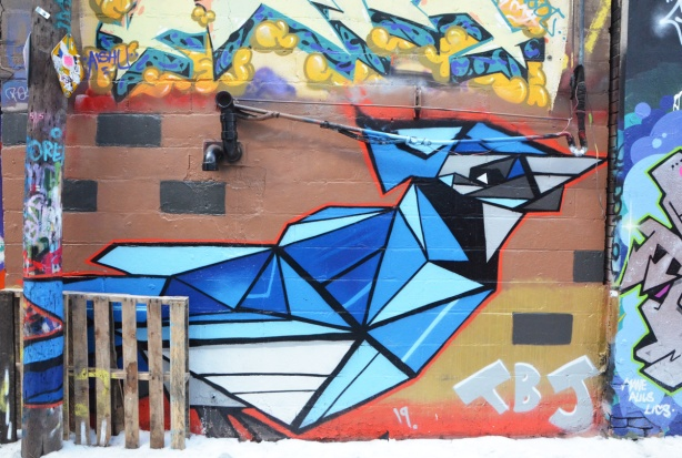 street art mural of a blue jacy, in stylized geometric shapes, shades of blue