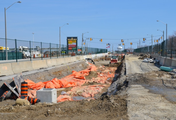 shallow but wide hole in the ground where new LRT tracks are being laid. construction in prep for the tracks, green fencing separates construction from traffic on both sides,