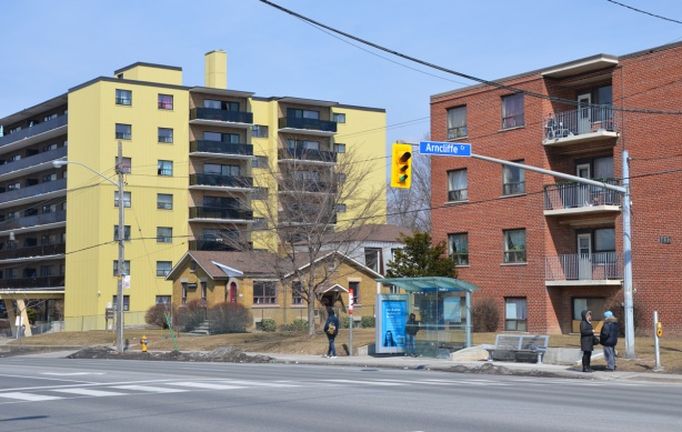 two lowrise apartment buildings side by side on Victoria Park Ave., one in red brick and the other is yellow