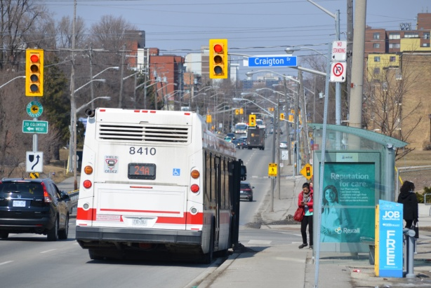 back of a TTC bus as it stops at Victoria Park and Craigton, a woman is standing at a bus stop