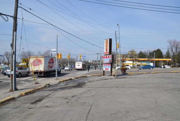 empty parking lot at the intersection of two roads, Victoria Park Ave and Lawrence ave., truck and some other traffic, Damas middle eastern restaurant and a Shell gas station