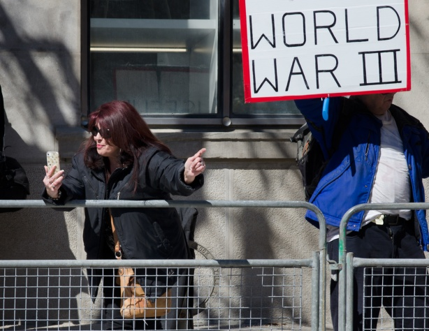 a woman with dyed auburn hair is making a video of herself at a protest on her cell phone