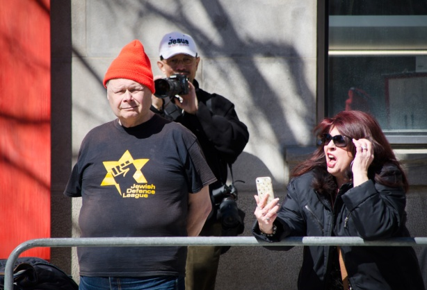 a woman with dyed auburn hair is making a video of herself at a protest on her cell phone, two men are also in the photo, one has an orange toque and a Jewish defence league T-shirt and the other has a white baseball cap that says Jesus is my boss as he takes pictures of the crowd on the other side of the protest