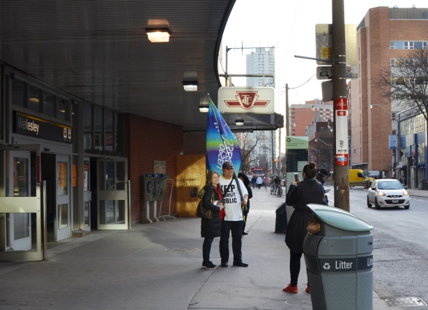 a man holds an OPSEU (a union) flag outside Wellesleysubway station as he stands with a woman while someone is taking their picture.