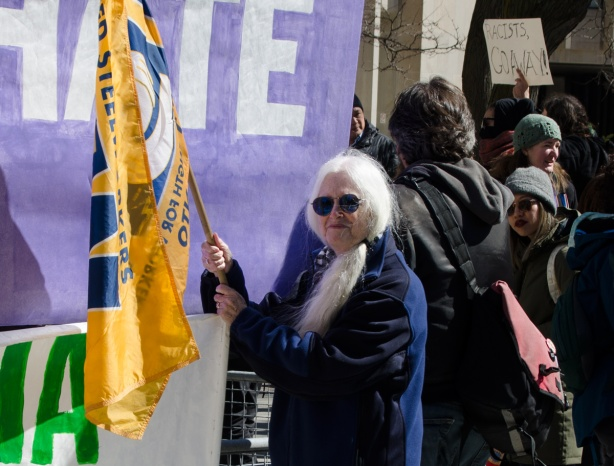 an older woman with long white hair and sunglasses stands in front of a light purple banner