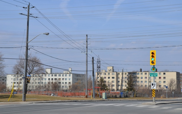 three lowrise white apartment buildings in the distance, hydro wires, vacant land