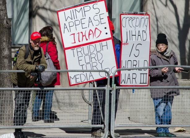 an older woman and a man with a red MAGA baseball cap stand on either side of placards at a protest
