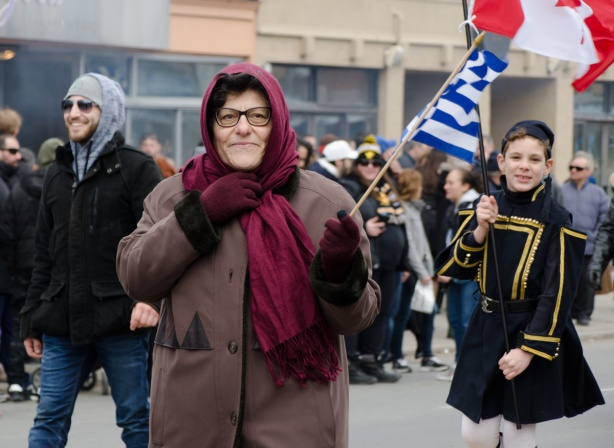 a woman in a brown coat and maroon scarf wrapped around her head, holds a Greek flag. Behind her is a boy in traditional greek clothing in a parade